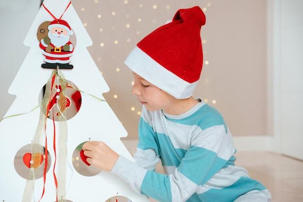 Garotinho com papai noel ao lado de uma árvore decorada