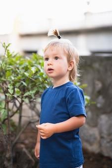 Garotinho com rabo de cabelo, olhando para longe