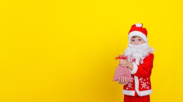Garotinho com roupas de papai noel e barba segurando uma sacola com presentes de ano novo nas mãos