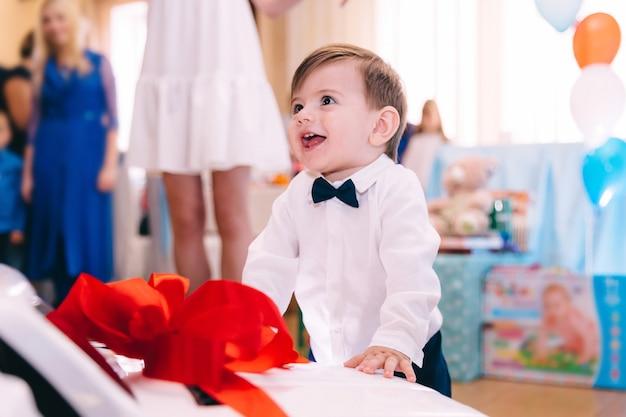Garotinho com roupas elegantes, sorrindo e em pé perto do carro