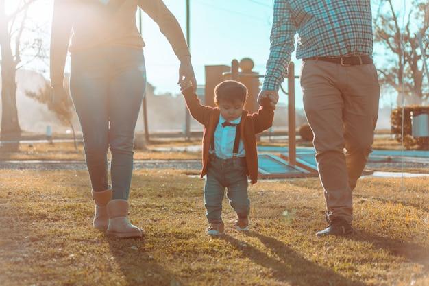 Garotinho com seus pais andando