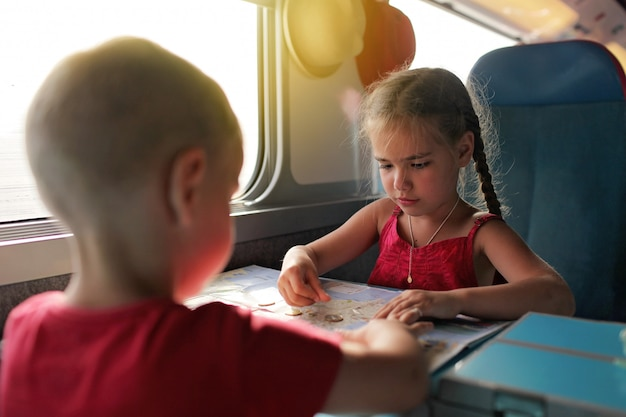 Garotinho com sua irmã discutindo suas férias de economia durante a viagem de trem