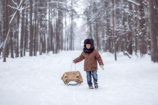 Garotinho com trenó na floresta de inverno