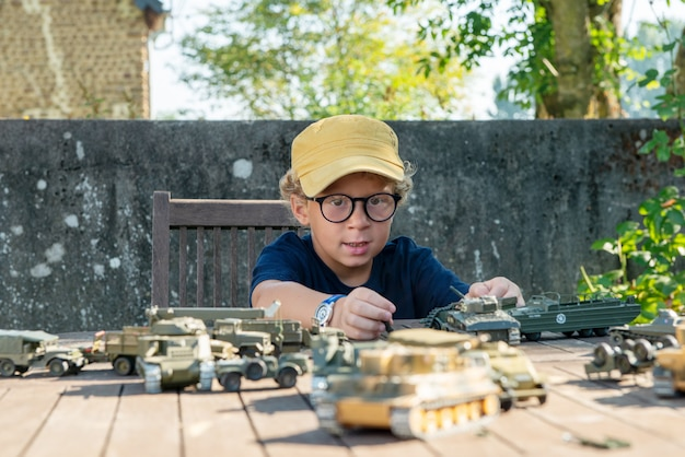 Garotinho com um boné amarelo brinca com brinquedos fora
