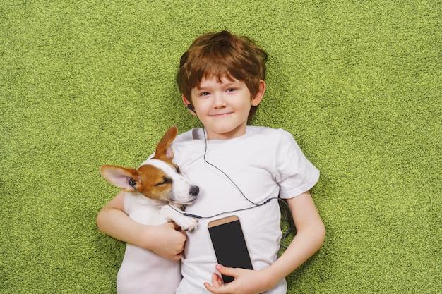 Garotinho com um cachorro ouve música.