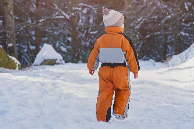Garotinho com um macacão laranja, caminhando na estrada coberta de neve em uma floresta de coníferas. dia de sol de inverno. vista traseira.