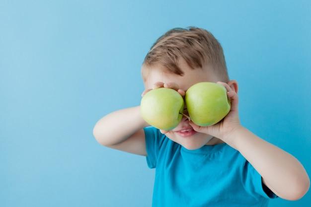 Garotinho com uma maçã nas mãos sobre fundo azul, dieta e exercícios para o conceito de boa saúde.