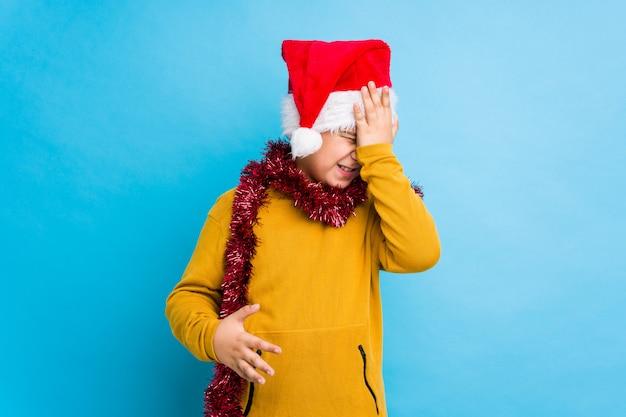 Garotinho, comemorando o dia de natal, usando um chapéu de papai noel isolado esquecendo algo, batendo na testa com a palma e fechando os olhos.