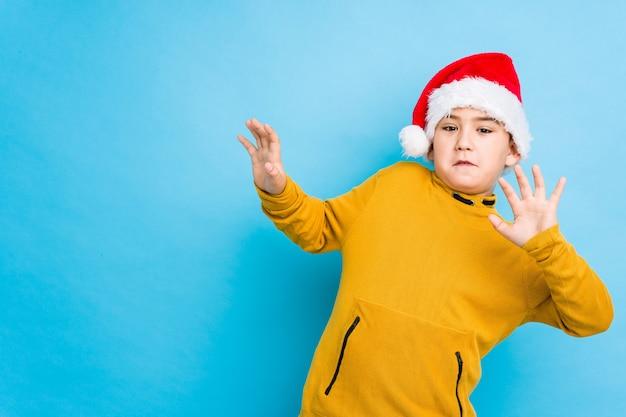 Garotinho comemorando o dia de natal usando um chapéu de papai noel isolado sendo chocado devido a um perigo iminente