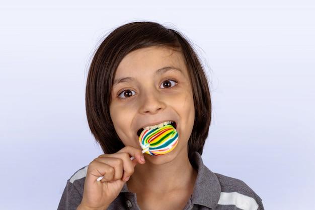 Garotinho comendo um pirulito.