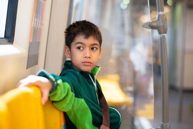 Garotinho comprando passagem elétrica e andando na estação de trem de céu público com a família