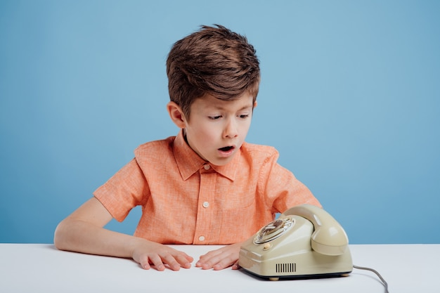 Garotinho confuso com telefone antigo sentado à mesa fundo azul