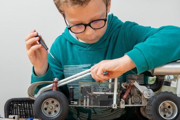 Garotinho consertando um modelo de carro controlado por rádio