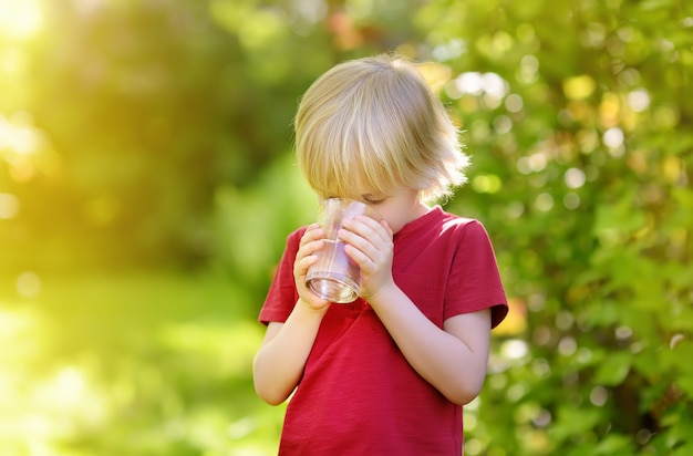 Garotinho, copo de água em um dia quente de verão ensolarado no quintal ou jardim de casa