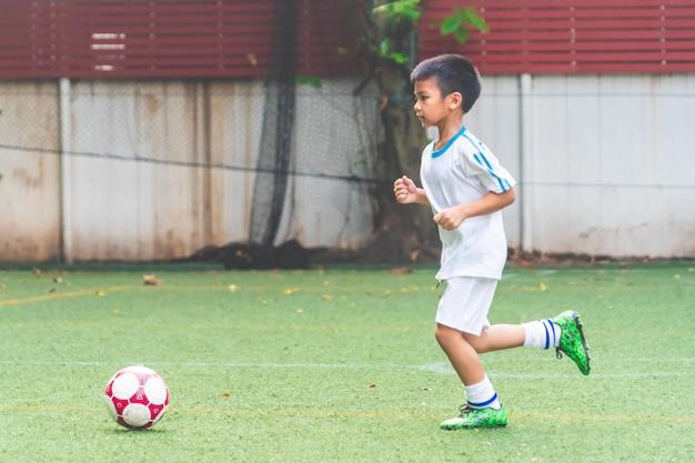 Garotinho correndo com bola de futebol no campo de futebol