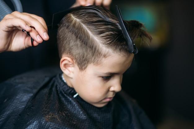 Garotinho, cortando o cabelo pelo barbeiro enquanto está sentado na cadeira na barbearia.
