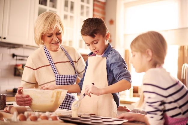 Garotinho cozinhando entre mulheres