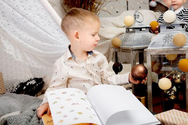 Garotinho criança sentada na flor e segurando a mão enfeite de natal ou decoração e livro.