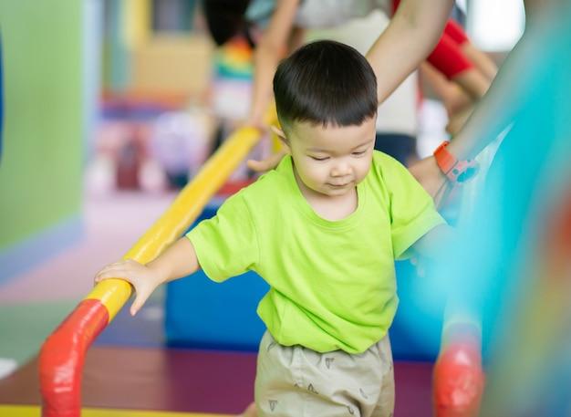 Garotinho da criança malhando no exercício ginásio indoor