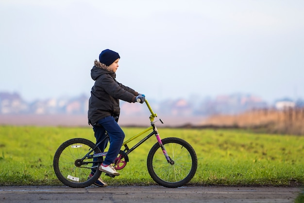 Garotinho de bicicleta lá fora. criança brincando ao ar livre