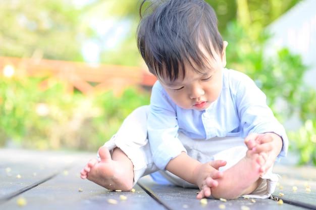 Garotinho de camisa azul sentado ao ar livre. criança sentada no parque em um toco à luz do sol.