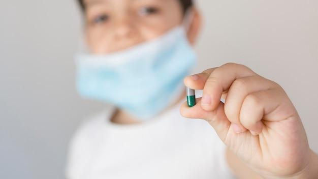 Garotinho de close-up com pílula