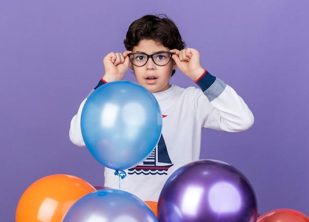 Garotinho de óculos, surpreso, olhando a câmera em pé atrás de balões isolados na parede azul