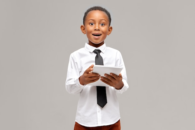 Garotinho de pele escura espantado, vestindo camisa branca e gravata preta, desfrutando de uma conexão de internet sem fio de alta velocidade no tablet digital tendo um olhar surpreso e pasmo, assistindo desenho animado online