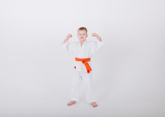 Garotinho de quimono branco com cinto laranja ergueu as mãos contra uma parede branca com uma cópia do espaço