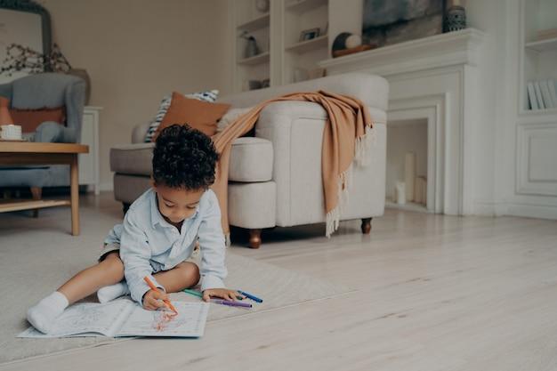 Garotinho de raça mista, desenhando em um livro para colorir com muitas caneta hidrográfica diferente enquanto está sentado sozinho no chão, no meio da sala de estar em casa. lazer infantil e atividades de desenvolvimento