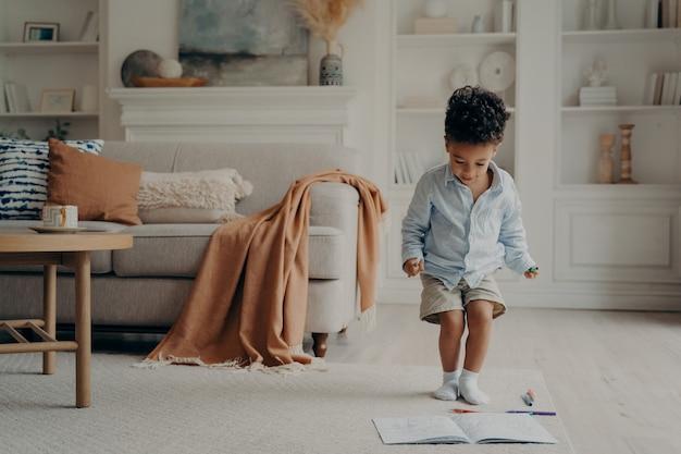 Garotinho de raça mista feliz curtindo brincar sozinho em casa se divertindo na sala de estar