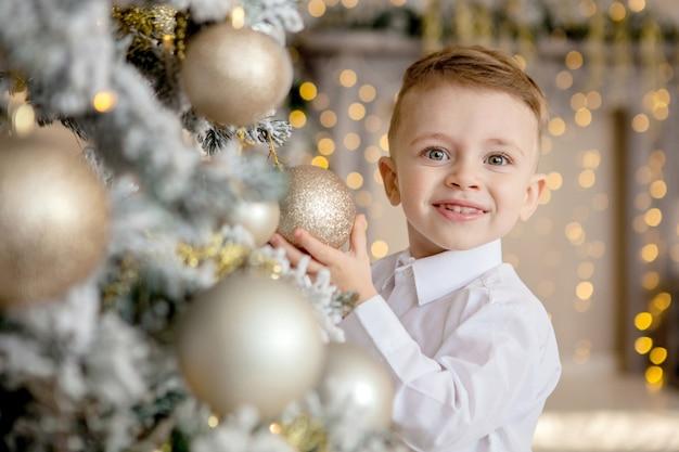 Garotinho decora uma árvore de natal para o natal