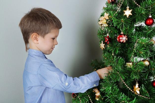 Garotinho decorando uma árvore de natal com enfeites no quarto
