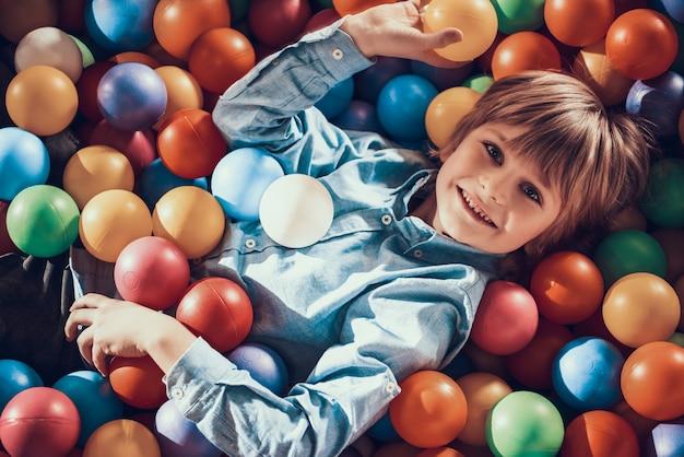 Garotinho deitado na piscina cheia de bolas coloridas