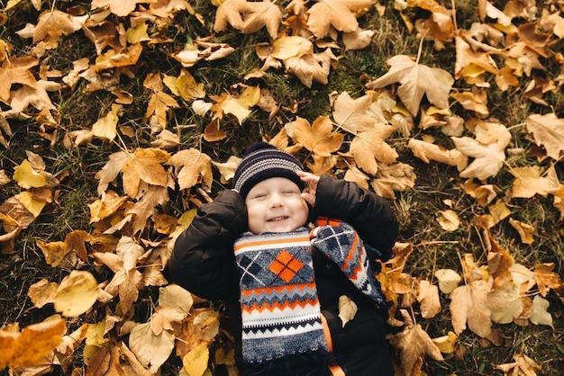 Garotinho, deitado sobre as folhas amarelas no parque outono, vista superior