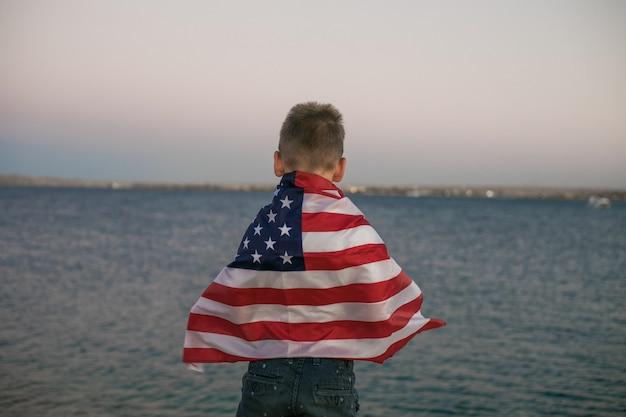 Garotinho deixa a bandeira americana voar em suas mãos com o vento no mar