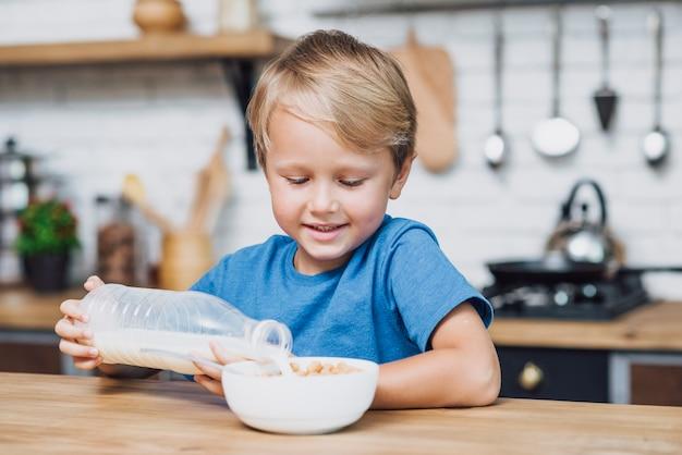 Garotinho, derramando leite na tigela de cereais