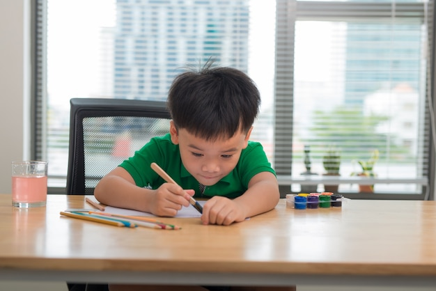Garotinho desenha um pincel e pinta seu primeiro quadro. foco no desenho