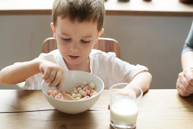 Garotinho, desfrutando de uma tigela de cereais