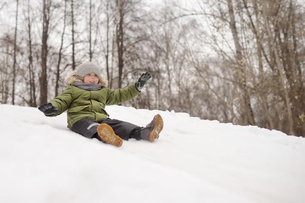 Garotinho desfrutar de andar no slide de gelo no inverno