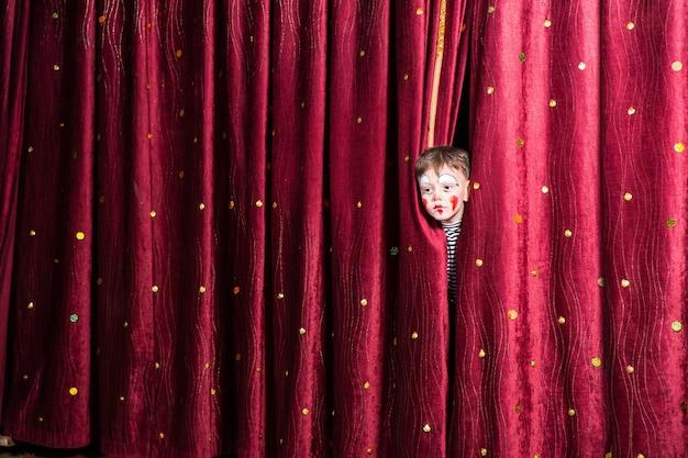 Garotinho divertido maquiado esperando por sua deixa de atuar enfiando a cabeça por entre as cortinas enquanto espera para fazer sua entrada no palco durante a apresentação