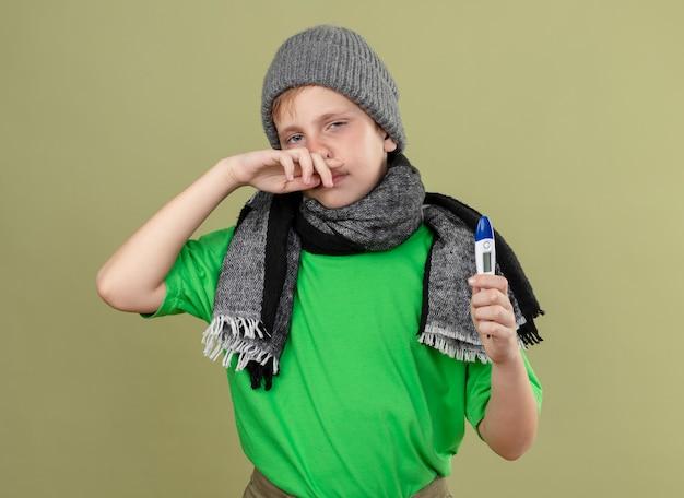 Garotinho doente, vestindo uma camiseta verde com um cachecol quente e um chapéu, sentindo-se indisposto, segurando um termômetro, limpando o nariz, sofrendo de corrimento nasal em pé sobre a parede de luz