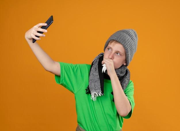 Garotinho doente, vestindo uma camiseta verde com um lenço quente e um chapéu, sentindo-se mal, segurando um smartphone, fazendo uma selfie enquanto tosse, em pé sobre uma parede laranja