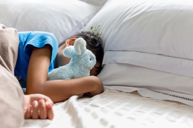 Garotinho dormindo na cama segurando seu coelho robbit