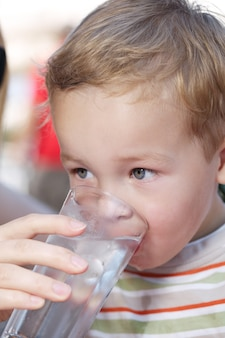 Garotinho drinkng um copo de água fresca