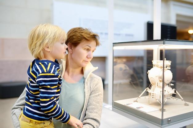 Garotinho e mulher olhando exibem uma exposição no pavilhão do espaço na exposição vdnh.