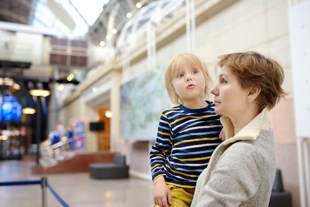 Garotinho e mulher olhando uma exposição em um museu científico