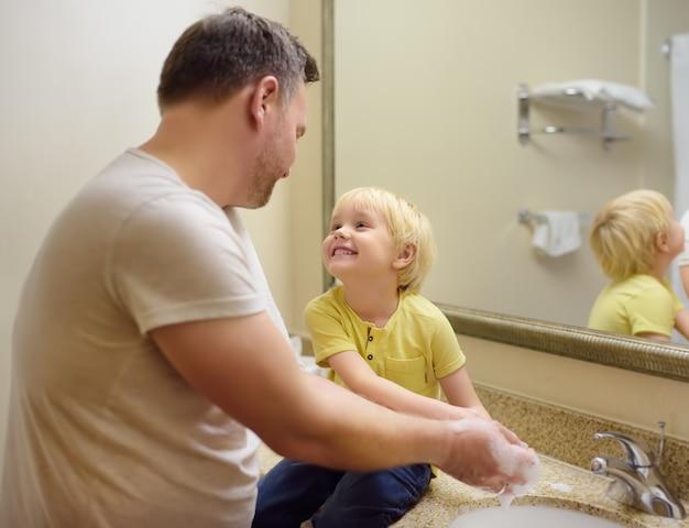 Garotinho e seu pai lavando as mãos com sabão no banheiro juntos