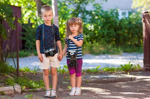 Garotinho e uma garotinha sagacidade duas câmeras vintage em pé para