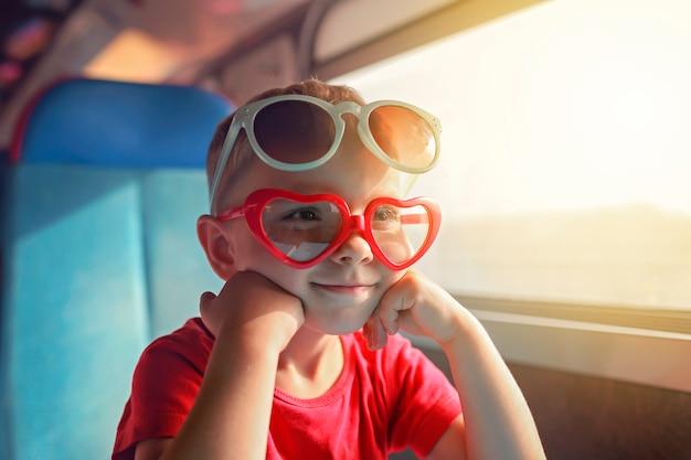 Garotinho em alguns óculos de sol, viajando de trem durante as férias